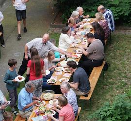 Viele Menschen essen gemeinsam an großem Tisch draußen