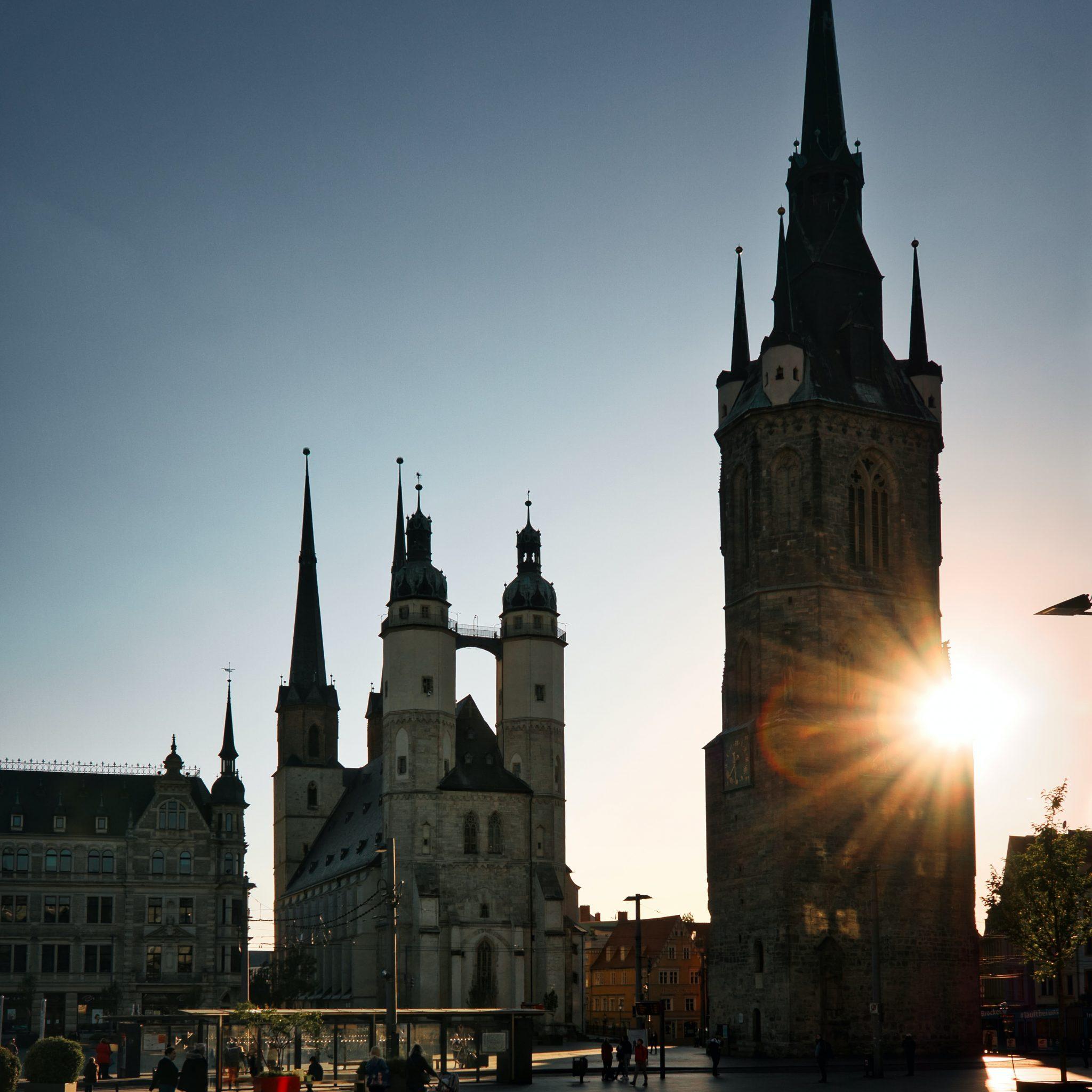 Halle Saale Wahrzeichen Marktkirche und Roter Turm vor untergehender Sonne und wolkenfreiem Himmel