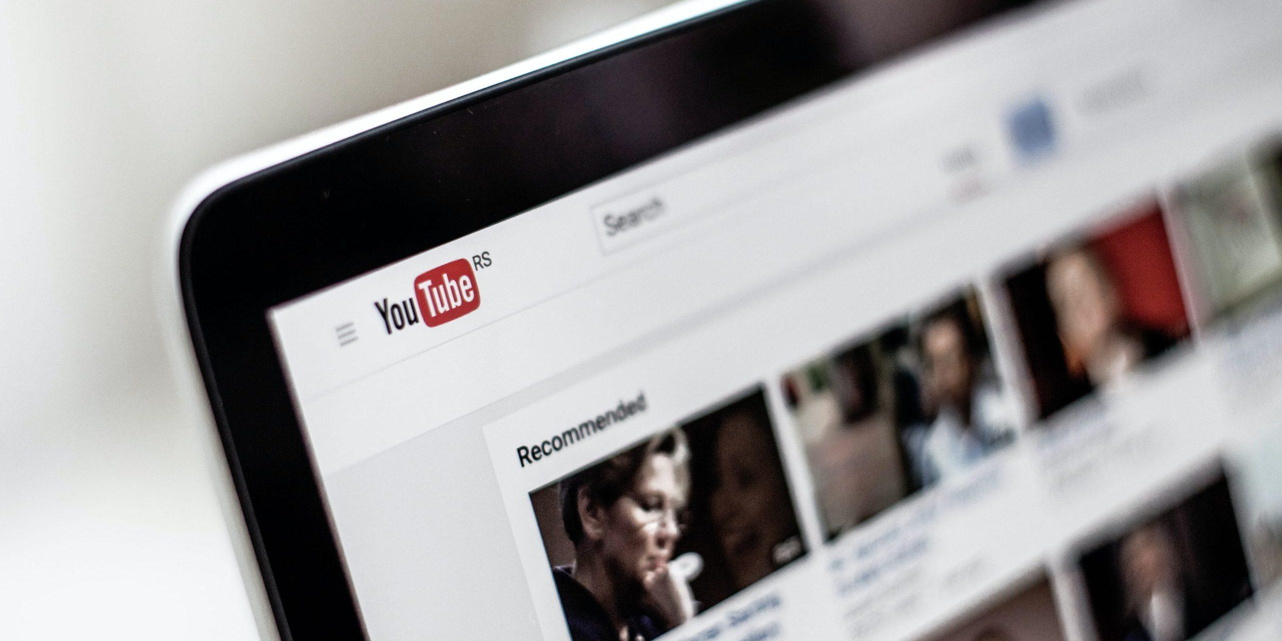 YouTube geöffnet auf einem Computer Monitor. Zu sehen ist die obere linke Ecke mit dem YouTube Logo und ein paar Video Vorschauen